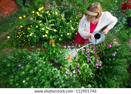 Mature caucasian woman watering her green garden with a lot of flowers - stock photo