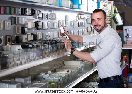 Mature cheerful man standing next to showcase with electrical switches and plugs  - stock photo