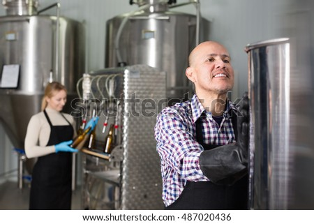 Mature cheerful man wearing a uniform standing among a brewery stainless equipment