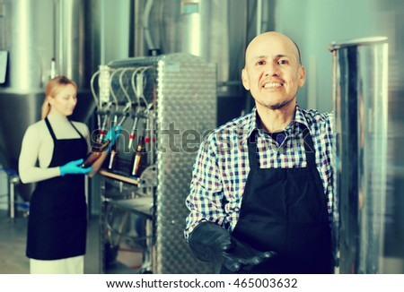 Mature cheerful man wearing a uniform standing among the brewery stainless equipment