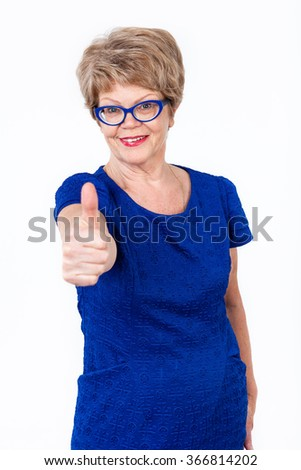 Mature cheerful woman showing thumb up gesture to the camera, white background