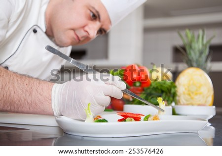 mature chef preparing a meal with various vegetables