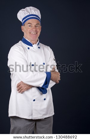 mature chef wearing workwear on dark blue background - stock photo