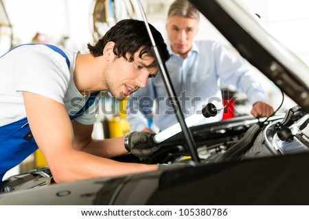 Mature client and young mechanic looking under car hood at engine with lamp - stock photo