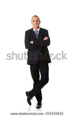 Mature confident businessman standing with folded arms. - stock photo