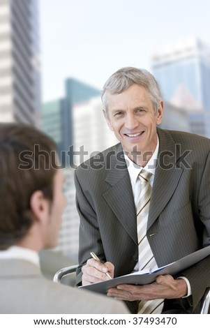 Mature consultant taking notes. - stock photo