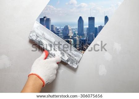 Mature contractor plasterer working indoors. City and skyscraper - stock photo
