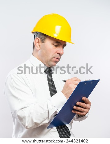 Mature contractor with hardhat and clipboard  - stock photo