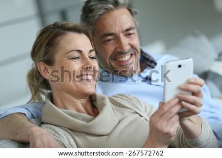 Mature coupel sittign in sofa and using smartphone - stock photo
