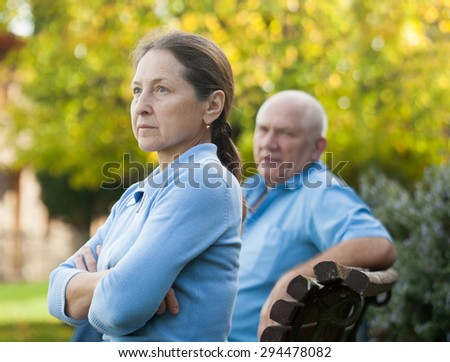 mature couple after quarrel sitting on   bench in autumn park.