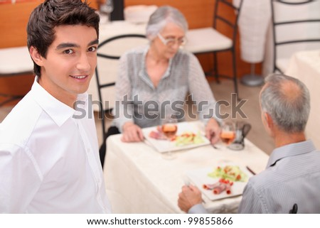 mature couple and young waiter at restaurant - stock photo