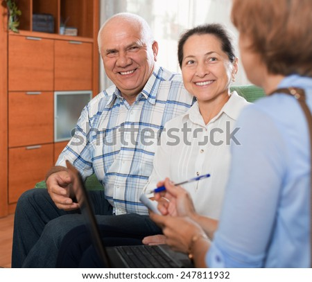 Mature couple answer questions of caseworker with computer in home - stock photo