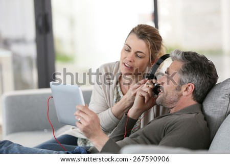 Mature couple at home listening to music with tablet - stock photo