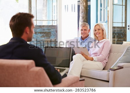 Mature Couple At Home Meeting With Financial Advisor