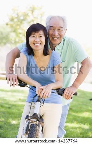 Mature couple bike riding. - stock photo