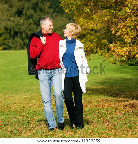 Mature couple deeply in love having a walk holding each other tight - stock photo