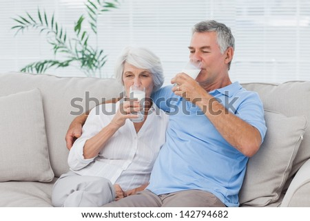 Mature couple drinking glasses of milk sitting on the couch - stock photo