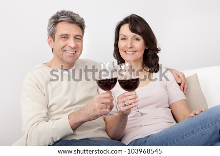 Mature couple drinking red wine at home