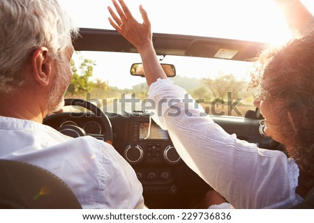 Mature Couple Driving Along Country Road In Open Top Car - stock photo