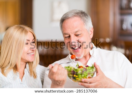 Mature couple eating a salad in the living room. Shallow depth of field, focus on the man - stock photo