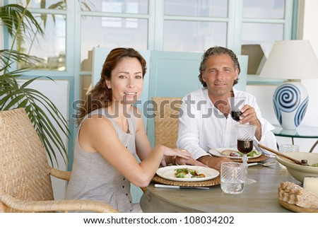 Mature couple eating and drinking together at garden table, smiling at the camera. - stock photo