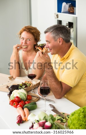 Mature couple eating delicious pizza in the kitchen. Man and woman drinking red wine and communicating with each other.