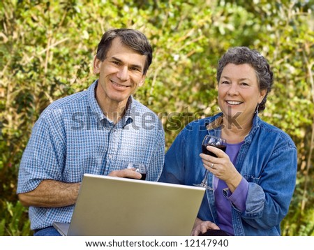 Mature couple exploring their retirement options on their laptop and toasting to the future. - stock photo