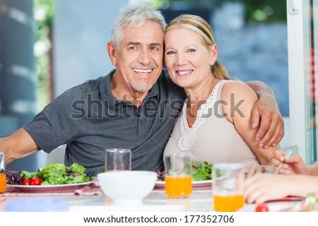 mature couple family lunch home, eating happy love smile, sitting at dinner table - stock photo
