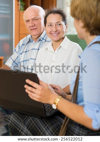Mature couple filling questionnaire for employee with laptop at apartment - stock photo
