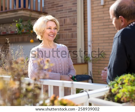 Mature couple having a conversation on a terrace: retired woman is holding her gardening tools and man holds a cup of water - stock photo