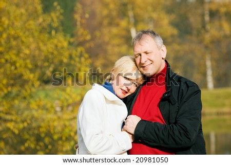 Mature couple having a walk holding each other tight still in love with each other - stock photo