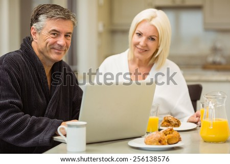 Mature couple having breakfast together man using laptop at home in the kitchen - stock photo
