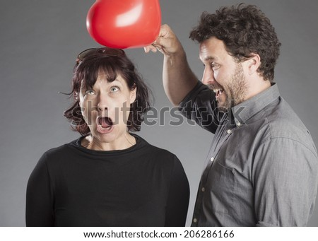 Mature couple having fun man joking hitting woman's head with red heart shaped balloon