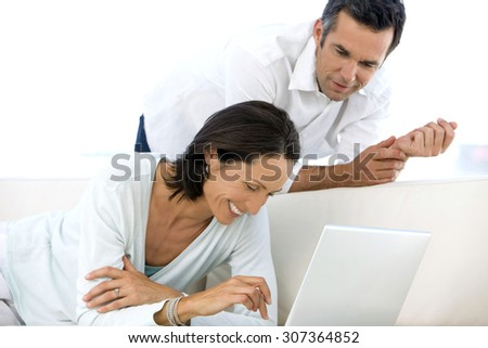 Mature couple having fun together at home. Woman surfing the web. Man next to her. They look happy and laugh. - stock photo