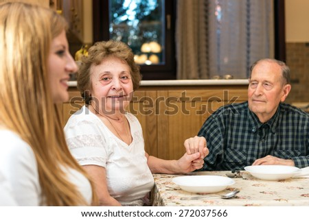 Mature couple having great time with their family, romantic emotional moments, the grandma is looking at the camera and smiling. Blurred foreground, shallow depth of field. - stock photo