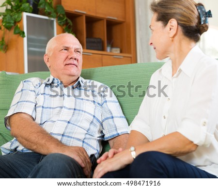 mature couple having serious talking at home. Focus on man