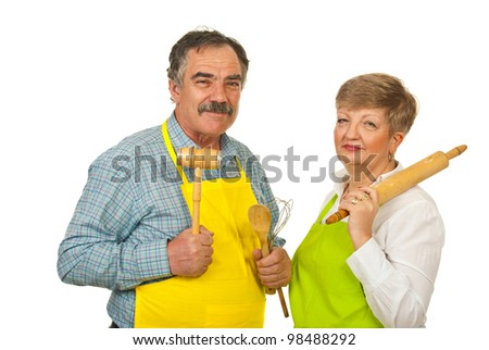 Mature couple holding kitchen utensil isolated on whiite background - stock photo