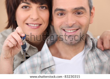 Mature couple holding up a set of keys - stock photo