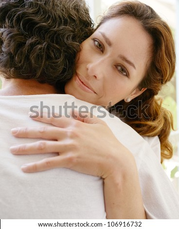 Mature couple hugging in a garden corridor at home.