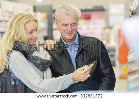 Mature couple in a supermarket choosing chocolate