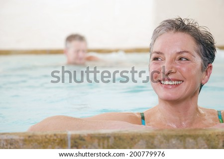 Mature couple in swimming pool woman smiling by pool's edge man further behind - stock photo