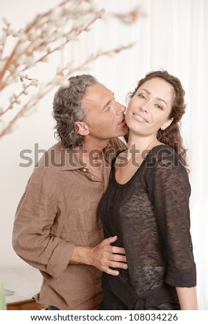 Mature couple kissing while lounging at home. - stock photo