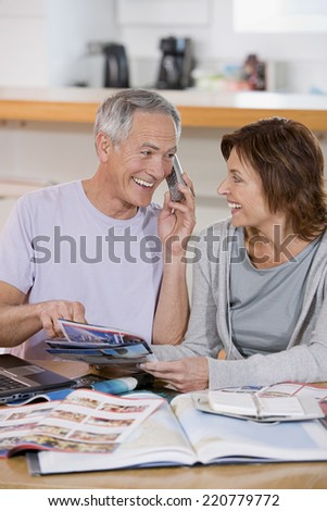 Mature couple looking at travel brochures and booking a holiday over the telephone - stock photo