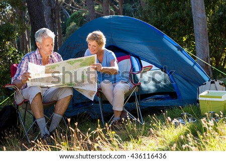 Mature couple looking map on their camp site on the wood - stock photo