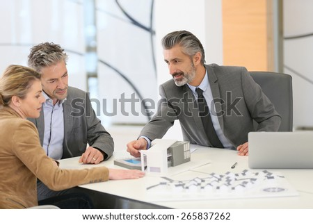 Mature couple meeting architect for construction project - stock photo