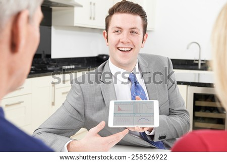 Mature Couple Meeting With Financial Adviser At Home - stock photo