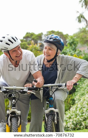 Mature couple mountain biking outside - stock photo