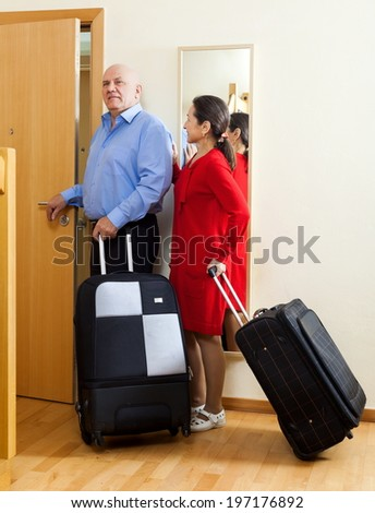 mature couple of travelers with suitcases in home going on holiday