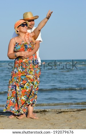 mature couple on sea series: picture happy man & woman having fun standing relaxing at seashore on sandy beach and embracing on summer sea outdoors background  - stock photo
