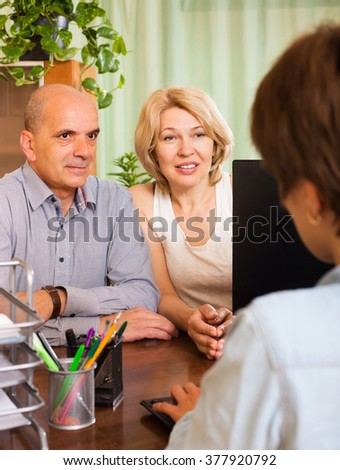 Mature couple opening saving account in bank - stock photo